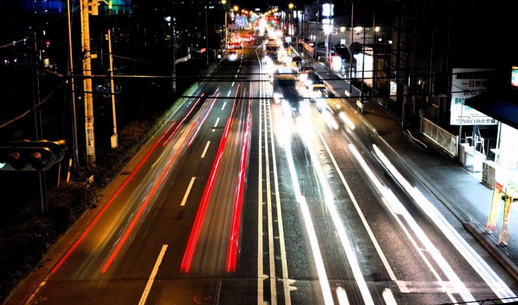 夜の道路を走る車のヘッドライト