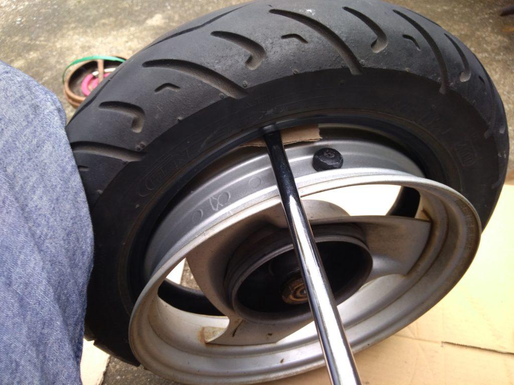 ホイールとタイヤの間にタイヤレバーを突っ込んで、さらに段ボールもかます。