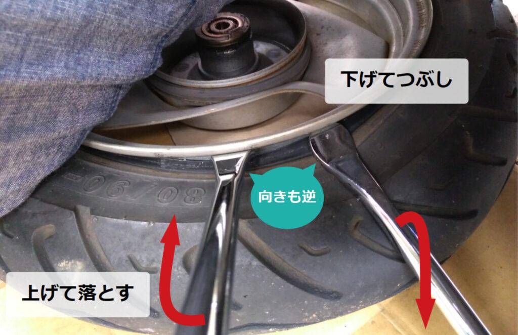 タイヤレバーを交互に使い、片方を下げてタイヤをつぶして、今度は逆に刺して上げてタイヤ端をホイール中央に落とす