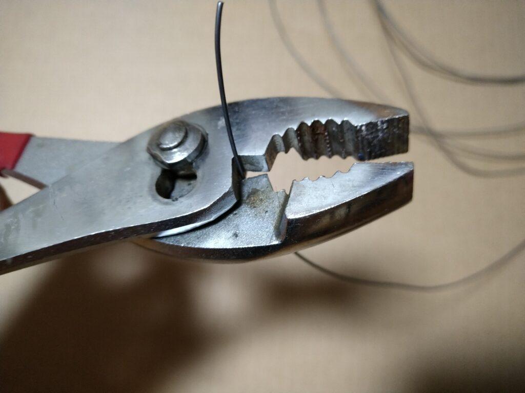 コンビネーションプライヤーでワイヤーを切る
